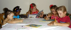 Five children at table reading and writing