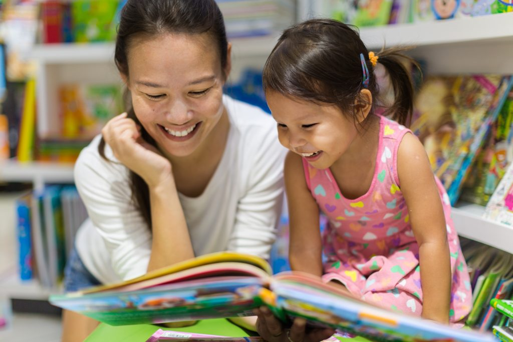 Parent and child happily reading together